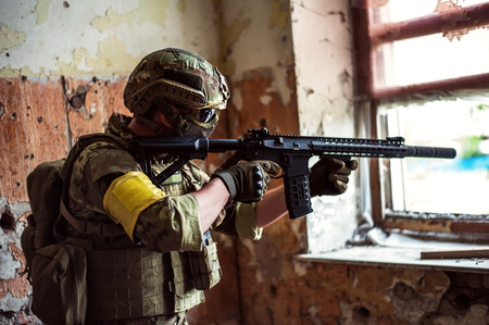 Military man sniper with automatic rifle with a  by the window in building