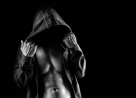 Dark contrast shot of dangerous young muscular latent man with no face wearing jacket with hood over black background photo