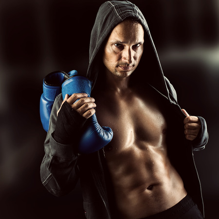 Serious Young muscular man boxer wearing jacket with hood. Boxing gloves slung over his shoulder on dark background indoor. photo