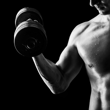 Focus on stomach. Black and white contrast shot of young muscular fitness man chest and arm. Bodybuilder with beads of sweat training in gym. Working out with dumbbells on black background photo