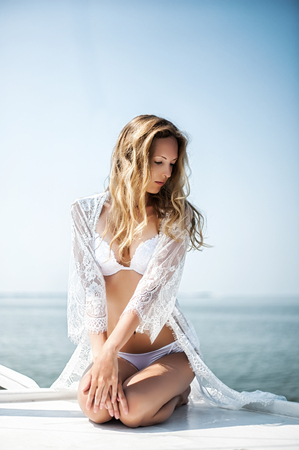 yachtsman: beautiful blonde slim woman wearing lacy lingerie and robe on yacht in sea Stock Photo