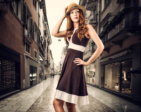 Beautiful fashion woman is wearing a brown dress and a straw hat. Posing isolated on white background photo