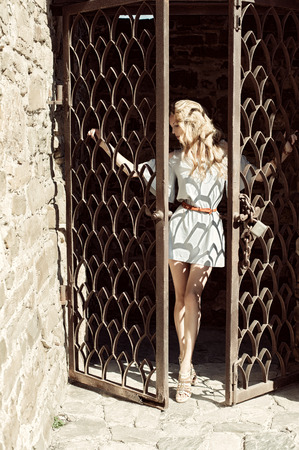 A young woman in short modern dress holds her hands behind the bars the door in an old stone fortress photo
