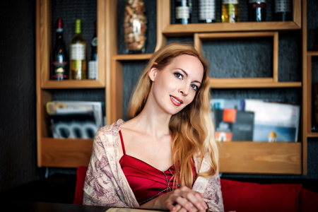 Portrait of beautiful blond smiling woman with white teeth sitting inside cafe at table. Looks at the camera