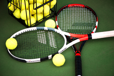 Close up view of two tennis rackets and balls on the clay tennis court. Focus on balls in basket