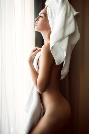 staying fit: Defocus portrait of beautiful woman wearing white towel on head stay near window in bedroom in the morning. Focus on eyes