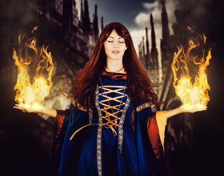 Beautiful woman witch in fantasy medieval dress and long hair. Eyes closed. And hands are divorced in the sides with fire magic.