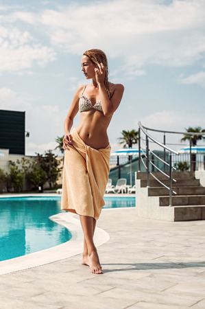 staying fit: Beautiful woman near outdoor water pool in hotel on tropical resort.