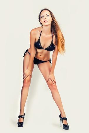 staying fit: Beautiful slim woman model with long legs and perfect body wearing black mini bikini on light gray background in studio