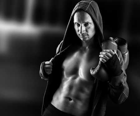 Dangerous Young muscular man boxer wearing jacket with hood. Boxing gloves slung over his shoulder on dark background indoor.