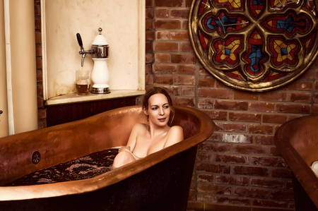 spa procedure - copper bath with dark beer. Beautiful woman bathing with happy smile Stock Photo