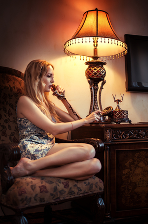 Young beautiful woman speaking by old vintage telephone with a dial-up dial and a tube on the wire. She sitting in armchair at home Banco de Imagens - 88604638
