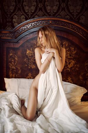 Belle fille mince dans son lit couvre le corps avec une couverture blanche Banque d'images - 89012270