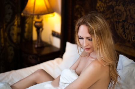 Beautiful gorgeous girl in bed covers the body with a white blanket close up