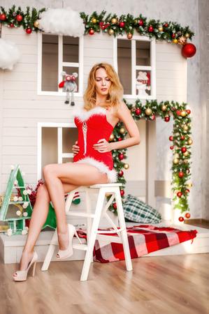 折り畳み式の階段に座っている赤いドレスの長い脚と美しいセクシー サンタ クロースの女の子 写真素材