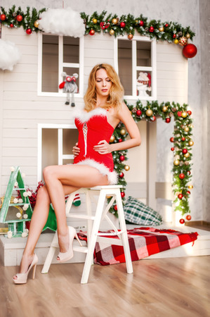 Beautiful sexy santa claus girl with long legs in red dress sits on the folding staircase Reklamní fotografie