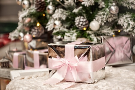 Macro view of present christmas box with tender pink ribbon. gift under the eve tree
