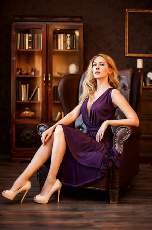 Stunning majestic domineering woman in a beautiful dress and in high-heeled shoes sits in an expensive leather chair in her home office