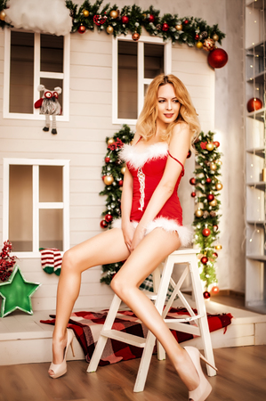 Beautiful santa claus girl with long legs in red dress sits on the folding staircase