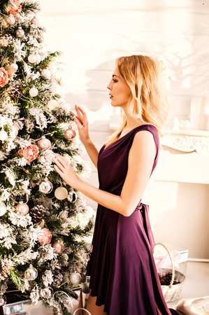 Beautiful woman in purple dress decorate the Christmas tree decorations at home kneeling