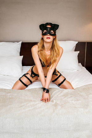 Beautiful sexy lingerie model in bdsm cat style mask - blond young woman with perfect figure wearing black leather belts, harness