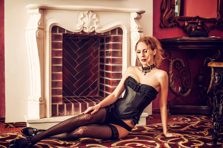 Beautiful aristocratic woman wearing corset, stockings and heels sitting on a carpet on floor near fireplace in retro interior house or castle