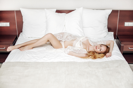 Beautiful young woman wearing white lingerie and lacy robe lies on bed in modern bedroom Foto de archivo