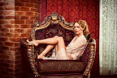 Beautiful young adult woman in lace dressing gown sits in retro antique armchair in the castle room