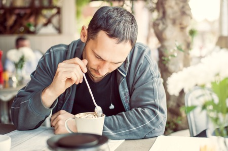 Young adult man sitting at street cafe at a table and stir with a spoon the whipped cream and foam on the coffee in cup