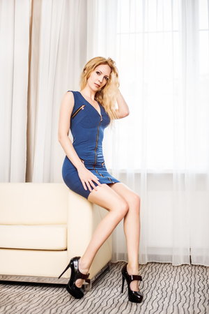 Beautiful woman with long slim legs in short blue dress and high-heeled shoes sitting on light sofa in white room