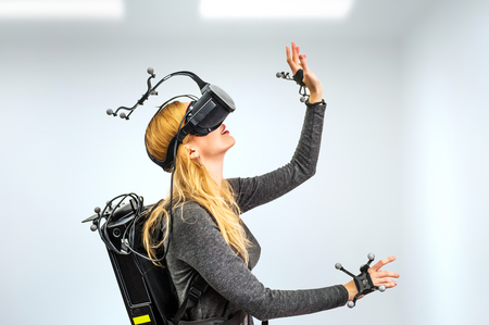 Beautiful woman touching air during VR experience in room. She wearing Virtual reality glasses or goggles, processor in backpack on back and sensors for tracking on head and hands