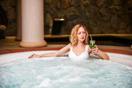 Beautiful woman in white swimsuit sits in jacuzzi in spa and drink cocktail mojito Stock Photo