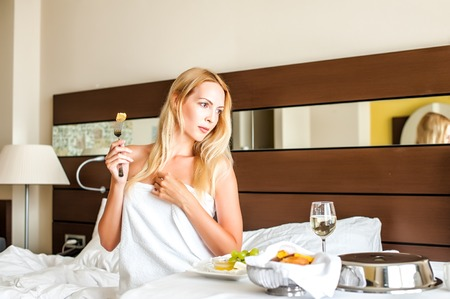 Beautiful young adult blond Woman model have breakfast dinner or lunch in badroom in hotel