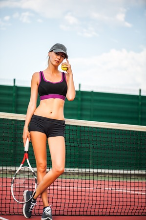 Young beautiful Woman tennis player wearing cap having rest while standing on tennis court after match Stock Photo