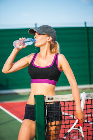 Young beautiful Woman tennis player wearing cap drinking water from bottle while standing on tennis court after match