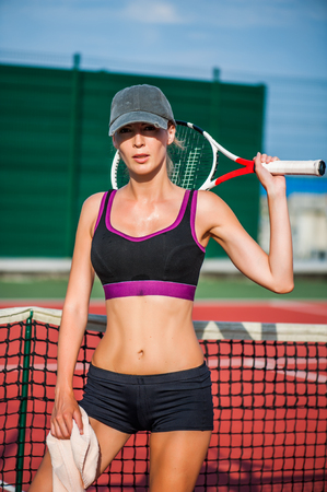 Young beautiful Woman tennis player wearing cap having rest while standing on tennis court after match. Holding towel