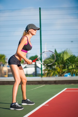 Young beautiful Woman holding racket wearing cap playing tennis and waiting for the service while standing on tennis court during match