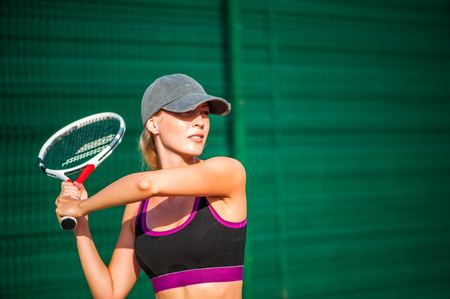 Young beautiful Woman holding racketwearing cap playing tennis and waiting for the service while standing on tennis court during match