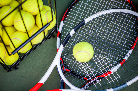 Close up view of two tennis rackets and balls on the clay tennis court. Focus on racket