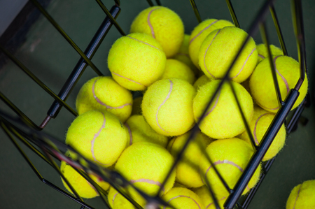 Defocus image of Close up view of balls in basket on clay tennis court. Focus on balls Stock Photo