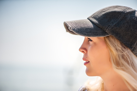Defocus portrait of Beautiful girl close-up in profile in a cap against the sea