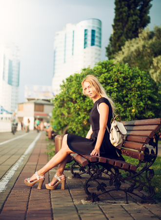 beautiful fashionable girl sitting on a bench on the embankment in a megacity