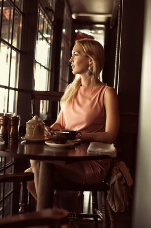 beautiful fashion woman in asymmetrical gently pink dress in dark interior of cafe or restaurant