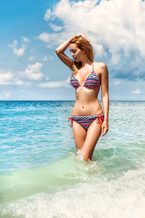 Beautiful bikini model blond girl on tropical resort stay in blue water of sea or ocean
