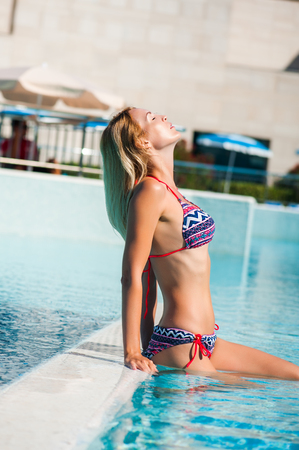 Beautiful bikini model blond girl on tropical resort sits on side of pool at hotel