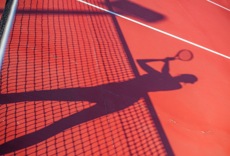 Tennis competition concept shadow of Woman holding racket playing tennis and waiting for the service while standing on court during match