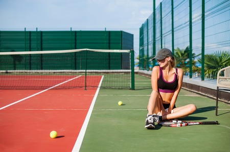 Young beautiful Woman sitting on tennis court and having rest after match