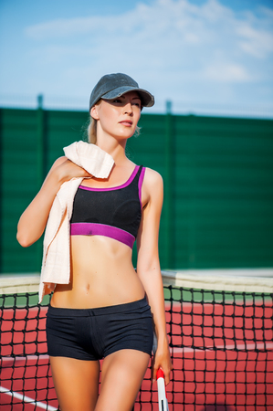 Young beautiful Woman tennis player wearing cap having rest while standing on tennis court after match. Wipe the sweat with a towel