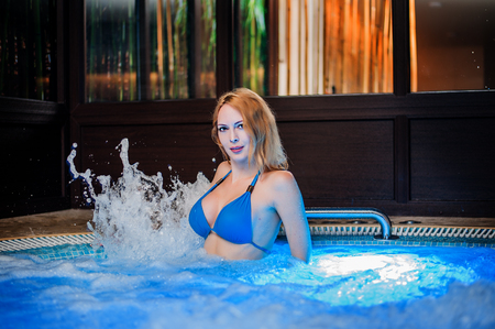 Beautiful woman sits in whirlpool tube in hot wellness and spa wearing blue swimsuit Stock Photo