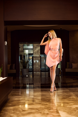 beautiful fashion woman in asymmetrical gently pink dress in dark interior of hotel holl Stock Photo